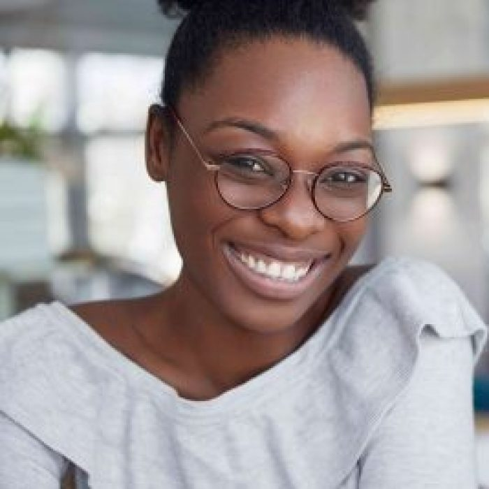 headshot-positive-attractive-dark-skinned-african-female-round-glasses-expresses-pleasant-emotions (1)
