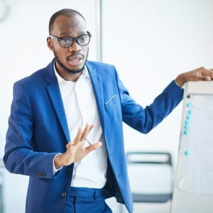 waist-up-portrait-successful-african-american-businessman-standing-by-whiteboard-while-presenting-design-project-during-meeting-office-copy-pace_236854-23570